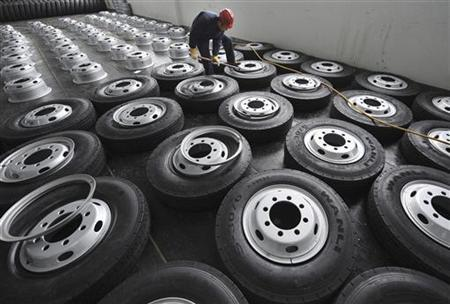 An employee installs tire rims at a factory of Zhengxing Wheel Group Co. Ltd in Hefei, Anhui province January 20, 2011. REUTERS/Stringer/Files