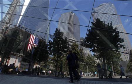 Visitors are reflected in the windows of the 9/11 Museum, which is under construction, during the first day that the 911 Memorial was opened to the public at the World Trade Center site in New York, September 12, 2011. REUTERS/Mike Segar