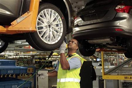 A Ford Motor assembly worker works on the under body of the Ford Focus vehicles for 2012 at the Michigan Assembly Plant in Wayne, Michigan, December 14, 2011.   REUTERS/Rebecca Cook