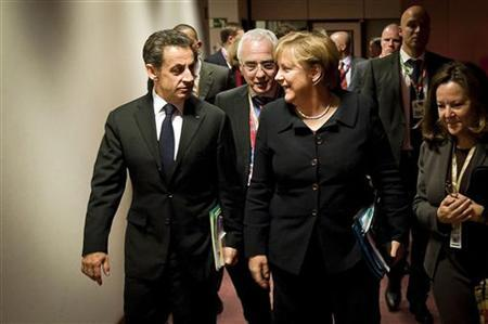 Germany's Chancellor Angela Merkel and France's President Nicolas Sarkozy talk while on their way to a working dinner during an European Union summit in Brussels, December 8, 2011. REUTERS/Guido Bergmann/Bundesregierung/Pool