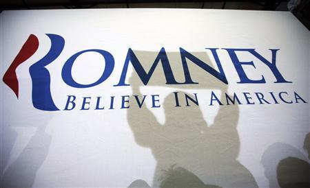 Supporters cast shadows on a campaign banner during a rally with Republican presidential candidate and former Massachusetts Governor Mitt Romney in Dubuque, Iowa January 2, 2012, ahead of the Iowa Caucus on January 3, 2012. REUTERS/Brian Snyder
