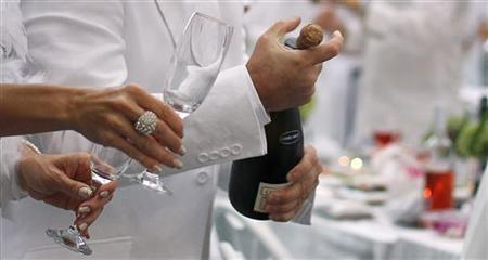 A man corks a champagne bottle as he participates in the White Dinner in Quebec City August 18, 2011. REUTERS/Mathieu Belanger/Files
