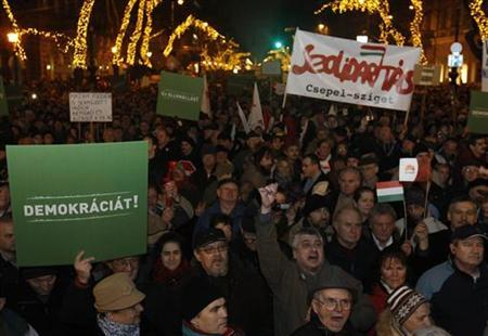 People hold up signs during a protest in central Budapest January 2, 2012. REUTERS/Laszlo Balogh