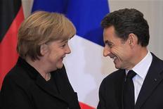 Президент Франции Саркози и канцлер Германии Меркель общаются после совместной пресс-конференции в Елисейском дворце в Париже, 5 декабря 2011 года. Президент Франции Николя Саркози встретится с канцлером Германии Ангелой Меркель в Берлине 9 января, чтобы обсудить меры ужесточения бюджетной дисциплины в Европейском союзе. REUTERS/Charles Platiau  (FRANCE - Tags: POLITICS BUSINESS)