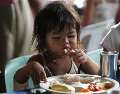 A girl eats a free meal during a feeding program at the slum area in Baseco, Tondo city, metro Manila August 24, 2011. REUTERS/Romeo Ranoco
