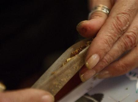 A Dutch woman makes a cannabis cigarette in a coffee shop in Amsterdam October 6, 2011. REUTERS/Toussaint Kluiters