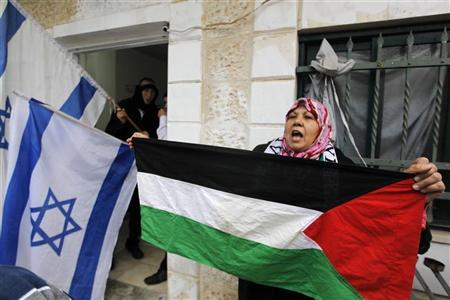 A Palestinian protestor holds a Palestinian flag in front of extreme right wing Jewish settler's house during a weekly protest in the Sheikh Jarrah neighborhood of East Jerusalem December 30, 2011.  REUTERS/Ammar Awad