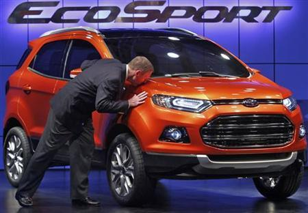 Alan Mulally, President and CEO of Ford Motor Company kisses the newly launched EcoSport vehicle, in New Delhi January 4, 2012. Ford Motor Co on Wednesday launched the EcoSport, its new global compact sports utility vehicle, and said it will invest $142 million in the company's Chennai plant in south India to manufacture the model for the domestic and export markets. REUTERS/Adnan Abidi