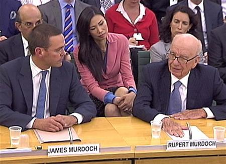 Rupert Murdoch's wife Wendi Deng (C) looks on as BSkyB Chairman James Murdoch and News Corp Chief Executive and Chairman Rupert Murdoch (R) appear before a parliamentary committee on phone hacking at Portcullis House in London July 19, 2011. R REUTERS/Parbul TV via Reuters Tv