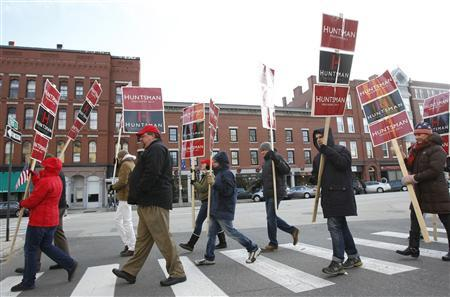 Supporters of Jon Huntsman carry campaign signs as they cross a street following a campaign event at Eagle Square Clock Tower in Concord, New Hampshire, January 4, 2012. REUTERS/Jessica Rinaldi