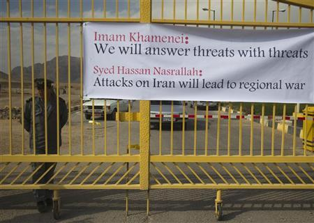 EDITORS' NOTE: Reuters and other foreign media are subject to Iranian restrictions on leaving the office to report, film or take pictures in Tehran. A security officer stands next to a banner hung on the entrance of the Uranium Conversion Facility (UCF), before a ceremony to form a human chain by Iranian students showing their support for Iran's nuclear program, in Isfahan, 450 km (280 miles) south of Tehran, November 15, 2011. REUTERS/Morteza Nikoubazl
