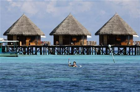 Tourists huts stand on a reef at a resort island at the Male Atoll December 8, 2009.  REUTERS/Reinhard Krause