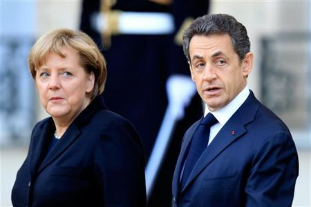 German Chancellor Angela Merkel (L) flanked by France's President Nicolas Sarkozy (R) leaves the Elysee Palace following a meeting in Paris December 5, 2011.  REUTERS/Charles Platiau