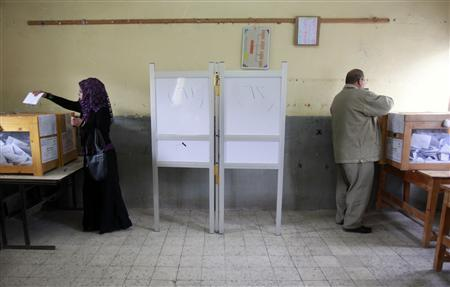 A man and a woman cast their votes in a school used as a voting center in Al-Arish city, north Sinai, January 4, 2012.    REUTERS/Asmaa Waguih