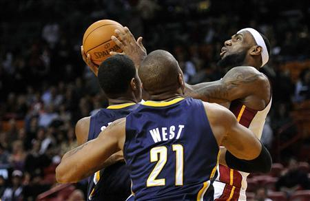 Miami Heat forward LeBron James (R) is defended by Indiana Pacers forward Paul George (L) and David West (C) during their NBA basketball game in Miami, Florida January 4, 2012.  REUTERS/Rhona Wise