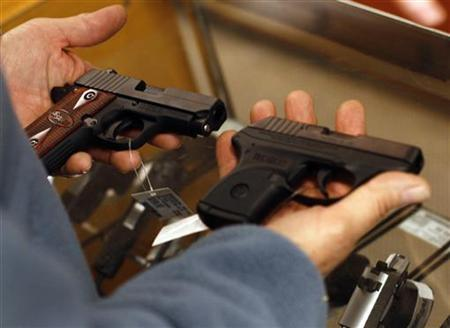 A customer holds two pistols at the Scottsdale Gun Club in Scottsdale, Arizona December 10, 2011. Guests at the club were able to have their photo taken with automatic weapons during an event with Santa Claus. REUTERS/Joshua Lott