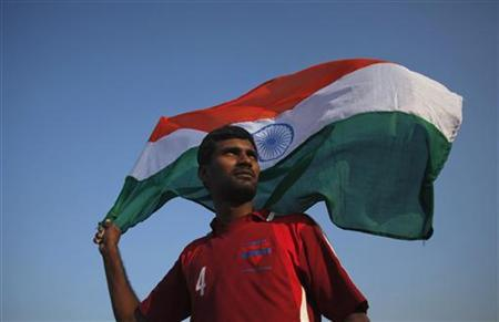 A man waves the national flag in Mumbai December 28, 2011. REUTERS/Vivek Prakash