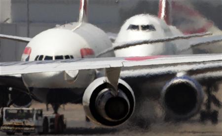 Passenger planes taxi along the runway under a heat haze at Sydney Airport, Australia. November 28, 2006.  REUTERS/Will Burgess