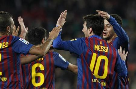 Barcelona's Lionel Messi celebrates with his team mates after scoring against Osasuna during their Spanish Kings Cup soccer match at Camp Nou stadium in Barcelona January 4, 2012. REUTERS/Albert Gea