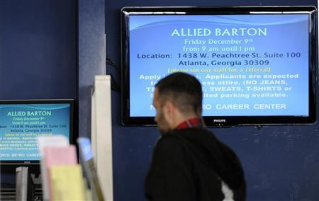 A job searcher waits in a line as a company job listing flashes on a TV screen at the North Metro Department of Labor Career Center in Atlanta, Georgia, December 1, 2011.  REUTERS/Tami Chappell