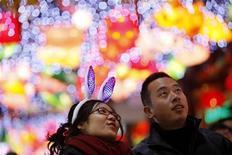 Пешеходы на улице Шанхая в день Праздника фонарей 17 февраля 2011 года. Миллионы жителей Поднебесной вскоре увидят Уоррена Баффета в необычном для него образе: американский инвестор исполнит песню в онлайн-версии ежегодного гала-концерта по случаю Нового года. REUTERS/Aly Song