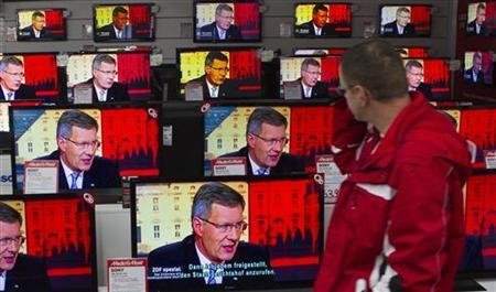 A man watches a television interview with German President Christian Wulff in an electronic retail store in Berlin January 4, 2012. REUTERS/Thomas Peter