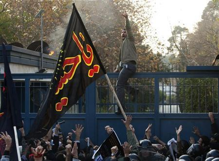 Iranian protesters shout slogans as one of the protesters climbs over the gate of the British embassy in Tehran November 29, 2011. REUTERS/Raheb Homavandi