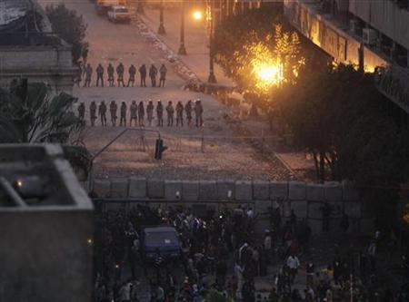 Troops stand guard behind a wall they built to separate them from protesters, during clashes between troops and protesters near the cabinet offices, in Cairo December 18, 2011.  REUTERS/Asmaa Waguih