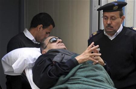 Former Egyptian president Hosni Mubarak lies on a gurney bed while leaving the courtroom at the police academy, where he is on trial, in Cairo January 2, 2012. REUTERS/Stringer