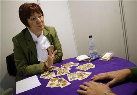 Maria Luisa Romero reads tarot cards for a customer during the XXIV International Forum on Esoteric Sciences and Alternative Therapies in Madrid October 30, 2008. REUTERS/Susana Vera