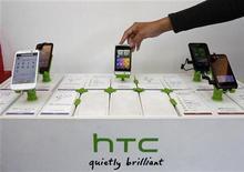 Работник магазина в Тайбэе раскладывает смартфоны HTC 24 ноября 2011 года. Прибыль тайваньского производителя телефонов HTC Corp сократилась сильнее прогнозов в четвертом квартале 2011 года в условиях жесткой конкуренции со смартфонами компаний Apple Inc и Samsung. REUTERS/Pichi Chuang