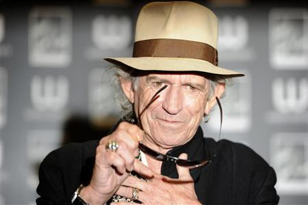 British musician Keith Richards poses for photographers before signing copies of his autobiography ''Life'' at a Waterstone's book shop in London November 3, 2010.  REUTERS/Paul Hackett