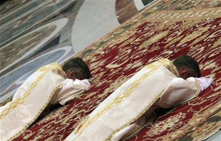 Two newly ordained bishops, Charles John Brown (R) and Marek Solczynski (L), lie prostrate in front of Pope Benedict XVI during a mass in St. Peter's Basilica at Vatican City January 6, 2012. REUTERS/Alessandro Bianchi