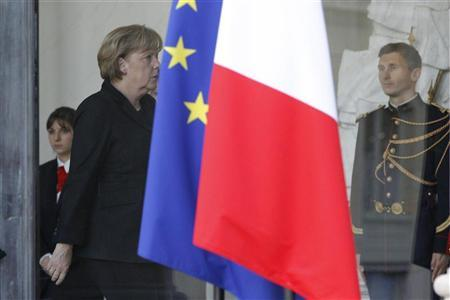 German Chancellor Angela Merkel walks past flags before attending a joint press conference at the Elysee Palace in Paris December 5, 2011. REUTERS/John Schults