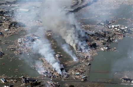Smoke rises from houses damaged by an earthquake and tsunami in Sendai, northeastern Japan, March 12, 2011.   REUTERS/Jo Yong-Hak