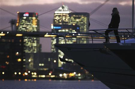 A woman poses on-board a yacht with Canary Wharf behind at the London Boat Show at the ExCeL centre in London, January 6, 20011.  REUTERS/Luke MacGregor