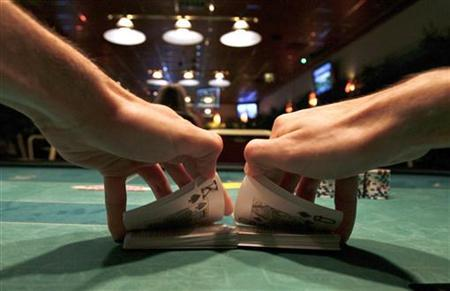A dealer shuffles a deck of cards during a poker game at a casino in Budapest September 15, 2009.    REUTERS/Katoly Arvai