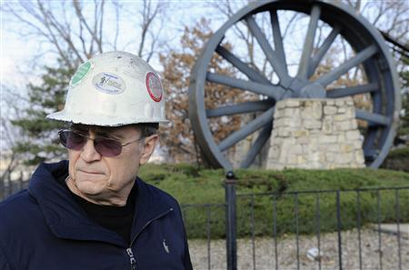 Former steel worker Joe Soptic stands near a giant drive wheel that was used by a steel mill that closed due to bankruptcy in 2001 and is now thought of as a memorial to the days that Kansas City, Missouri, December 15, 2011.REUTERS/Dave Kaup