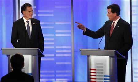 Republican presidential candidate former U.S. Senator Rick Santorum (R-PA) speaks as former Massachusetts Governor Mitt Romney (L) listens, in a Republican presidential debate at St. Anselm College in Manchester, New Hampshire, January 7, 2012. REUTERS/Mike Segar