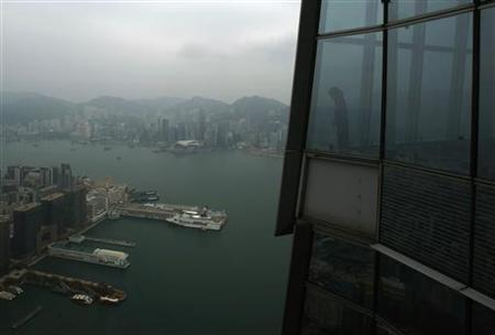 A worker at ''sky100'', the 100th floor of the International Commerce Centre (ICC), looks at Hong Kong's Victoria Harbour March 23, 2011.  REUTERS/Bobby Yip