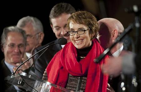 Arizona Representative Gabrielle Giffords (C), who suffered a head wound in the Tuscon shooting, smiles after reciting the Pledge of Allegiance at a memorial service marking the anniversary of the shooting, at the University of Arizona campus January 8, 2012. REUTERS/Laura Segall