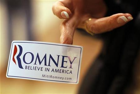 A woman hands out campaign stickers before a rally of Republican presidential candidate and former Massachusetts Governor Mitt Romney in Exeter, New Hampshire January 8, 2012. REUTERS/Brian SnydeR