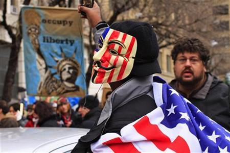 Protesters, one in a Guy Fawkes mask, affiliated with the Occupy Wall Street movement, protest around Duarte Square in New York December 17, 2011. REUTERS/Eduardo Munoz