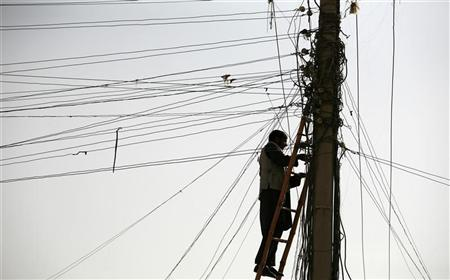 An Afghan man repairs electricity cables along the streets of Kabul November 16, 2009.   REUTERS/Jerry Lampen