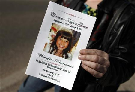 A woman holds the program from the funeral for nine-year-old Christina Green following the service at St. Elizabeth Ann Seton Church in Tucson, January 13, 2011.   REUTERS/Mike Segar
