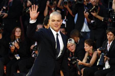 Actor Matt Damon (R), cast member of the movie ''Contagion'', waves as he arrives on the red carpet at Cinema Palace during the 68th Venice Film Festival September 3, 2011. REUTERS/Alessandro Bianchi