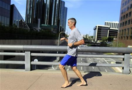 A man runs barefoot in downtown Los Angeles, California, November 8, 2011. REUTERS/Lucy Nicholson