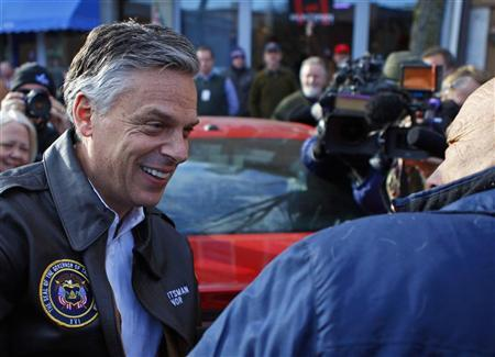 Republican presidential candidate and former Utah Governor Jon Huntsman (L) leaves a campaign stop at Harvey's Bakery in Dover, New Hampshire January 9, 2012. REUTERS/Adam Hunger