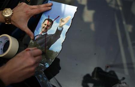A Syrian man living in Bulgaria draws a cross on a picture of Syrian President Bashar al-Assad during a rally against al-Assad in Sofia January 8, 2012. REUTERS/Stoyan Nenov