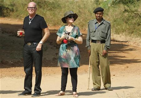 Keith Hudson (L), father of U.S. singer Katy Perry, and her mother Mary Hudson (C) look on as an Indian security personnel stands guard outside the Aman-i-Khas resort at the Sawai Madhopur district in the desert Indian state of Rajasthan October 22, 2010. REUTERS/Adnan Abidi